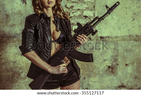 No face. unrecognizable person of young sexy woman in a leather jacket and sexual brassiere with a Kalashnikov in her hand. Girl stand against brutal brick wall - stock photo
