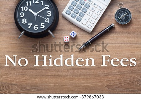 No hidden fees words written on wooden table with clock,dice,calculator pen and compass - stock photo