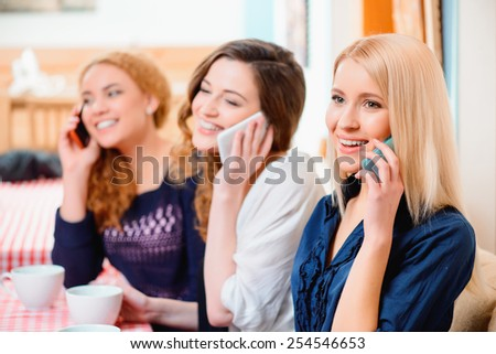 No minute without technologies. Three young beautiful female friends sitting in cafe and talking over their cell phones  - stock photo