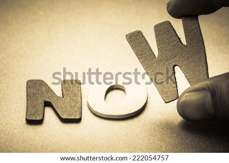 No or Now, closeup finger picking a small English letter for motivation concept - stock photo