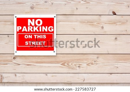 NO PARKING ON THIS STREET Red White Sign on Timber Wall Background - stock photo