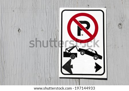 No parking sign displayed on a painted wooden fence. - stock photo