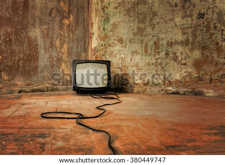 No Signal. An old TV with the noise on its display standing on the dirty floor - stock photo