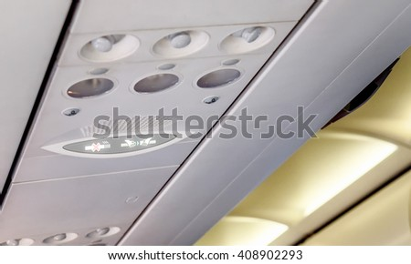 No smoking and fasten seat belts signs in aircraft - stock photo