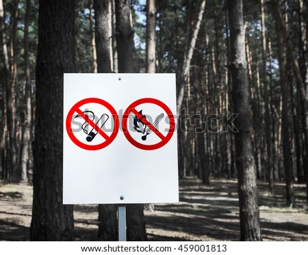 No Smoking and No Fire signs on a whiteboard in the forest. - stock photo