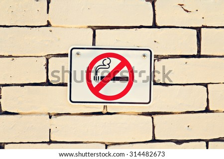 No smoking sign on brick wall with vintage style - stock photo