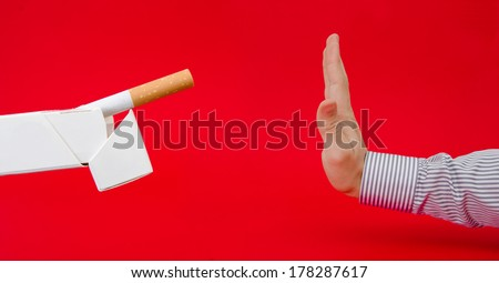 No smoking suggested by a business man refusing a pack of cigarettes on a red serious alerted important background with a dangerous look  - stock photo