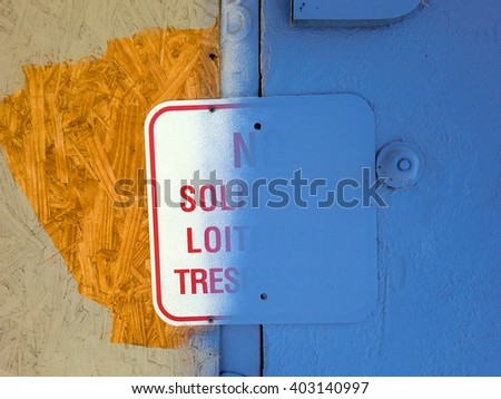 No soliciting loitering trespassing sign half covered in blue paint - landscape color photo - stock photo