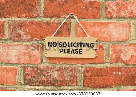 No Soliciting Please Wood Sign hanging on brick wall - stock photo
