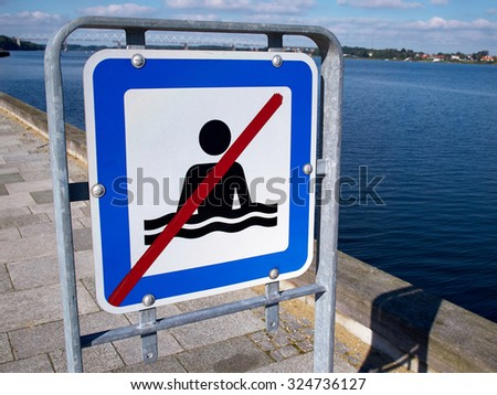 No swimming danger warning sign by the beach ocean   - stock photo