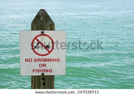no swimming or fishing sign on a post with out of focus water behind it - stock photo