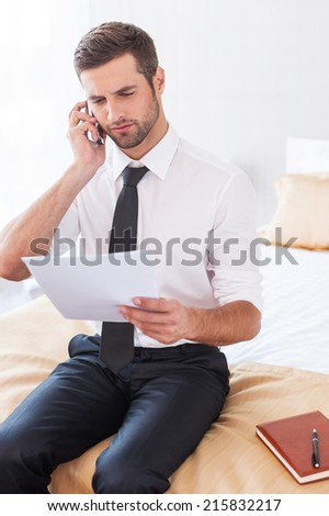 No time for rest. Confident young man in shier and tie talking on the mobile phone and holding document while sitting on the bed in hotel room - stock photo