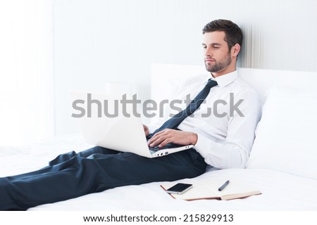 No time to relax. Confident young man in shirt and tie working on laptop while lying in bed at the hotel room  - stock photo