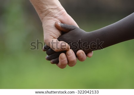 No To Racism Symbol - People Holding Hands Together Peace. African Peace Symbol. White woman holds hands with a little native African girl, in Bamako, Mali.  - stock photo