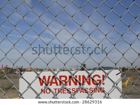 No trespassing sign and a chain link fence. - stock photo