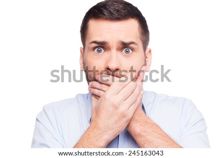 No way! Shocked young man in formalwear covering mouth with hands and looking at camera while standing against white background - stock photo