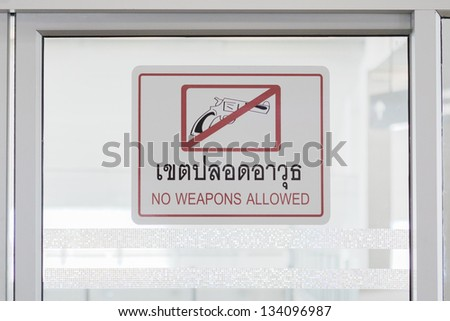 No weapons allowed sign on the glass door - stock photo