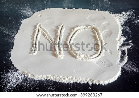 NO word write in white powder, black background, no drugs, close up. - stock photo