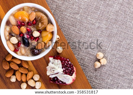 Noah's food or ashure, a specialty Turkish sweet grain pudding, served with hazelnuts, almonds and pomegranate seeds, overhead view with ingredients and copy space on textured beige linen - stock photo
