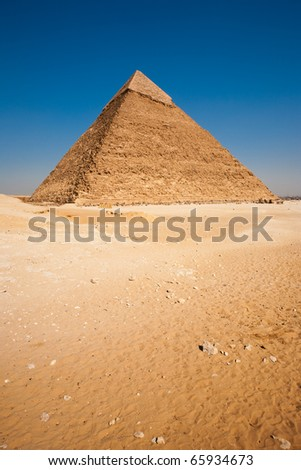 Nobody present in barren desert and clear blue sky and the rear of Khafre, the largest of the pyramids looking onto a view of the city Giza in Cairo, Egypt. Vertical copy space - stock photo