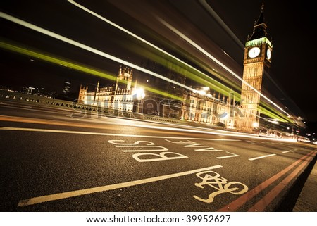 Nocturne scene with Big Ben behind light beams, angled composition. - stock photo