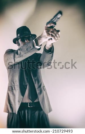 Noir Man Points Gun Up. Man in suit, hat and sunglasses pointing a gun upwards. - stock photo