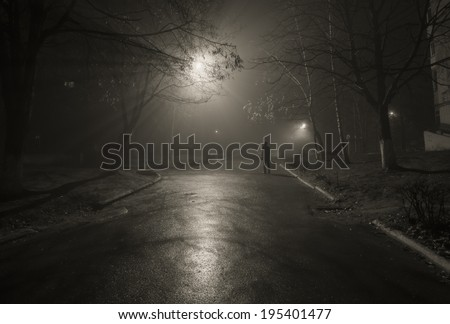 Noir. Silhouette of a passerby on the night street. Black and white - stock photo