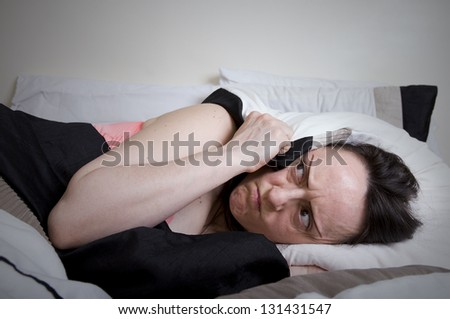 noisy neighbours, woman covering ears with pillow - stock photo