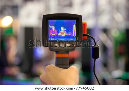 non-contact infrared thermometer in hand (thermal imaging camera) - stock photo