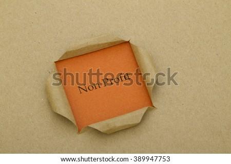 Non Profit word written under torn paper. - stock photo