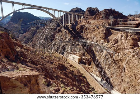 Non-standard mounting high-voltage lines on the Hoover Dam overlooking the bridge over the Colorado River in the Black Canyon. - stock photo