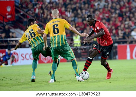 NONTHABURI THAILAND-MARCH  3 :Dagno Siaka(Red) of SCGMuangthong Utd. in action during Thai Premier League between SCGMuangthong Utd.and  Army United F.C. on March3,2013 in Nonthaburi,Thailand - stock photo