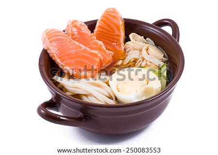 noodle soup with slices of fish in brown dish on a white background - stock photo