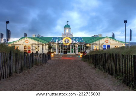 NOORDWIJK, NETHERLANDS - OCTOBER 14: Dramatic sunset sky over the Beach Club of Hotel von Oranje in Noordwijk, Netherlands as seen from across the dunes leading to the beach on October 14, 2014 - stock photo