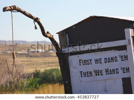 Noose hanging from a branch with funny sign - stock photo