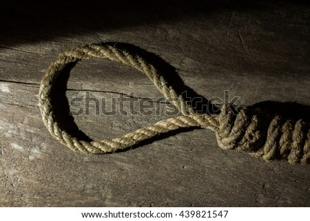 Noose in prison and wall grunge grain texture,Loop of old rope on wall background, Suicide Concept Image in Studio with Vignette Lighting and Copy Space.dark concept, still life concept.  - stock photo