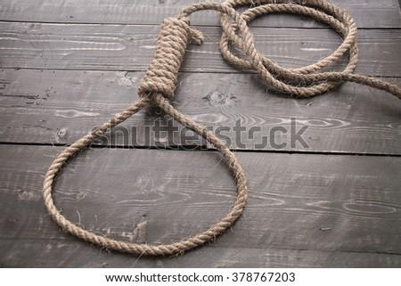 Noose,loop of rope on a dark vintage wood table background.  - stock photo