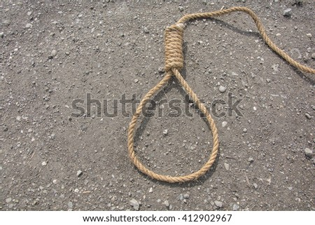 Noose,loop of rope on road. Loop hempen rope on a road background. Classic loop knot on road background - stock photo