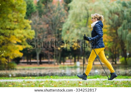 Nordic walking - middle-age woman working out in city park  - stock photo