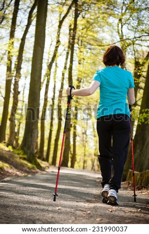 Nordic walking. Woman hiking in the forest or park. Active and healthy lifestyle. - stock photo