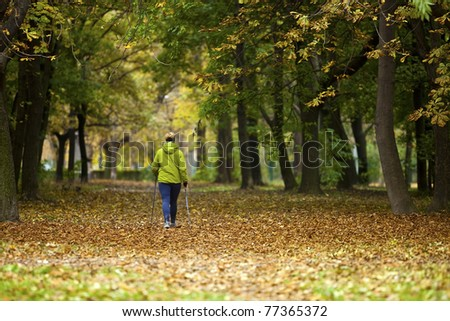 Nordic walking woman in vibrant autumn forest - stock photo