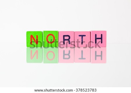 North - an inscription from children's wooden blocks - stock photo