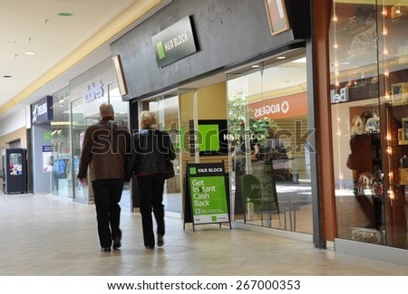 North Bay, Ontario, Canada - April 2, 2015: Couple walking fast in front of H and R Block. - stock photo