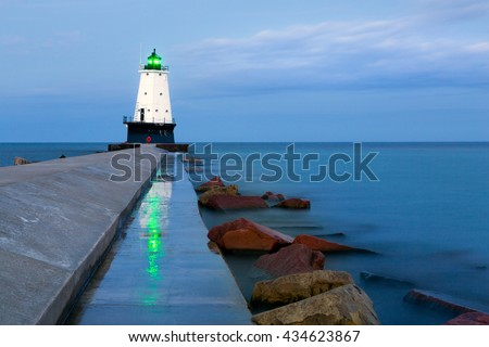 North Breakwater Pier Lighthouse located in Ludington Michigan. The lights green beacon reflects on the wet cement in the early morning blue hour light. - stock photo