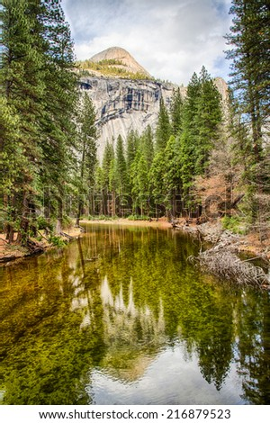 North Dome reflected in the Mercer River on a sunny spring day. Yosemite National Park, California. - stock photo