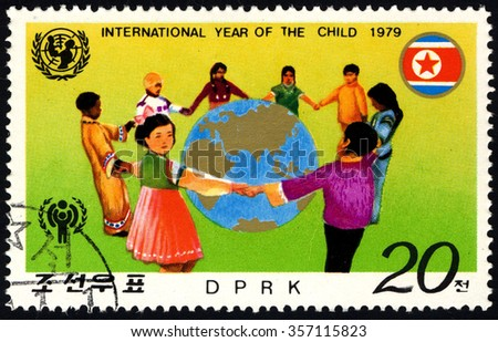 NORTH KOREA - CIRCA 1979: A stamp printed in DPRK dedicated to International year of the Child shows Children Surrounding The Globe, circa 1979 - stock photo