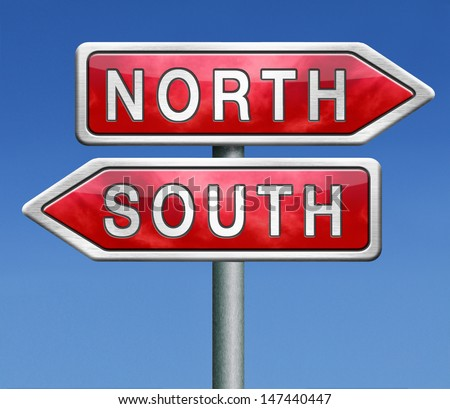 north or south warm or cold  road sign on blue background opposite direction opposites contrast choice crossroads - stock photo