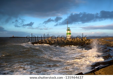 North sea waves and lighthouse in Ijmuiden, Holland - stock photo