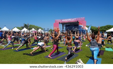 NORTH SHORE, HAWAII - FEBRUARY 28: People raise arms over head in warrior one during outdoor yoga class facing stage at Wanderlust yoga event on the North Shore, Hawaii on February 28, 2016. - stock photo
