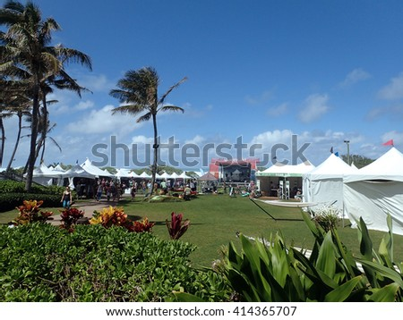 NORTH SHORE, OAHU - FEBRUARY 25: path leading to Wanderlust O'ahu festival stage and booths against a blue sky and ocean on the North Shore of Oahu, Hawaii.  February 25, 2016. - stock photo